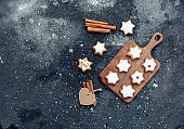 Homemade Christmas star shape gingerbread cookies with frosting and cinnamon over cutting board. Top view, flat lay
