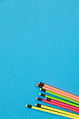 A half visible colorful pencils isolated lying on an azure background