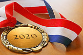 Gold Medal Inscribed With 2020 On Wood Surface