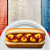 Hot Dog On White Paper Plate And Plastic Utensils On Patriotic Picnic Bench