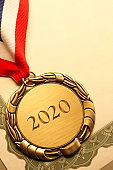 "Gold Medal Inscribed With ""2020"" Resting On An Award Certificate"