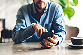 Handsome bearded hipster man use smartphone with coffee at table in cafe.Communication and technology concept