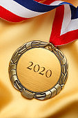 2020 Engraved On Gold Medal Resting On Gold Satin Fabric