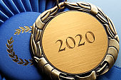 "Close Up Of Medal Engraved With ""2020"" Resting On A Blue Ribbon"