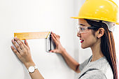 Young woman construction engineer in a yellow helmet working and  looking job for planning project at building home site