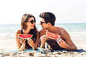 Romantic lovers young couple relaxing holding and eating a slice of watermelon on the tropical beach and looking  together.Summer vacations