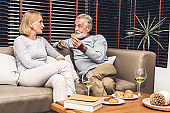 Senior couple relax talking and drinking wine glasses together on sofa in living room at home.Retirement couple concept