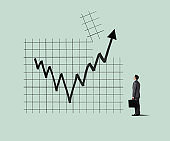 Businessman Looking Up At Chart As Arrow Breaks Through A Chart