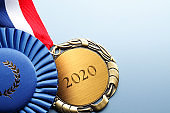 "Close Up Of Medal Engraved With ""2020"" On A Blue Background"