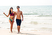 Romantic lovers young couple holding hands walking relaxing together on the tropical beach.Summer vacations