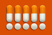 Rows Of Prescription Medication Pills And Capsules On Orange Background