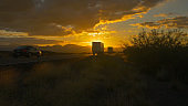 Cars and freight transport semi trucks driving on busy highway at golden sunset