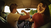 CLOSE UP: Cheerful young man and woman dance during road trip on sunny evening.