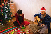 Couple sitting at home, wrapping christmas presents, guy plays guitar