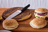 Hamburger preparing, cutting board with burger buns and knife