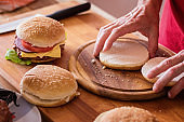 Hamburger preparing, bun cut onto halves, close-up