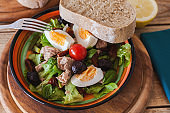 Nicoise salad at plate with bread lemon salt and pepper mill