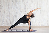 Young attractive woman practicing yoga and stretching body.