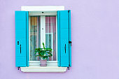Window with blue shutters on the violet wall.