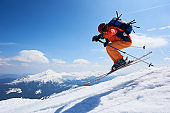 Sportsman skier jumping in air down steep snowy mountain slope on copy space background of blue sky.