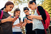 Group of school kids hang out and using smart phone