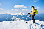 Man on ski on the summit enjoys spectacularly view mountain landscape under blue sky