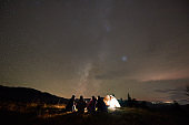 Back view of five people sitting at tourist tent on copy space background of dark starry sky.
