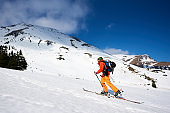 Skier tourist with backpack on background of bright blue sky and beautiful mountain panorama.