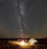 Tourist camping at night in the mountains under starry sky