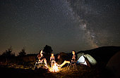 Family beside camp, campfire, tent under night starry sky