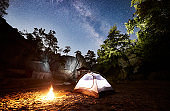 Tourist camping on rocky mountain under night starry sky