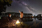 Man and woman having a rest on shore under night sky