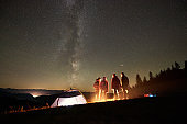 Friends resting beside camp, campfire under night starry sky