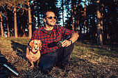 Happy hiker with dog resting on grass and drinking coffee