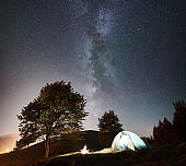 Tourist camping and tent under night sky full of stars
