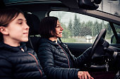 Mother driving daughter in passenger seat on a rainy day