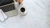 Office desk with marble texture and laptop, pen, notebook, coffee with flower on copy space table.