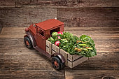 Antique Farm Pick Up Truck with Fresh Produce on a wood background