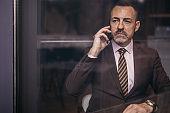 Handsome senior businessman having a business call