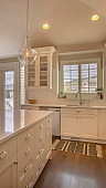 Vertical frame Kitchen interior of a home with island white cabinets cooktop sink and faucet