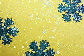 Snowflakes on a yellow background. Festive background. Holiday concept. Christmas and New Year concept. Top view, flat lay