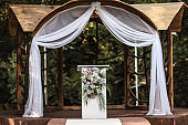 Wedding decorations in luxury ceremony. Arch for wedding ceremony a is decorated with flowers and greens, greenery.