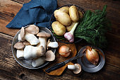 Eringi mushrooms, potatoes, onions, garlic and dill on the old table