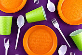 Plastic orange green waste collection on purple background. Concept of plastic pollution and ecology problem.