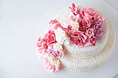 Two-tiered white wedding cake decorated with pink flowers
