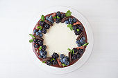 Cake with chocolate, decorated with backberries, blueberries, mint leaves, chocolate bars and cookies on a white table.