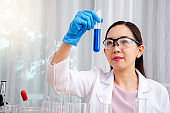 Scientist beautiful woman research and drop medical chemicals sample in test tube at laboratory, Science, chemistry, technology, biology concept
