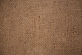 Dark brown background from a textile material with wicker pattern, closeup. Structure of the bronze fabric with texture.