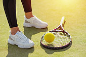 racket for tennis, ball and female legs in sport sneakers on a court close up