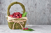 Red fresh cherry beries indecoration basket on a gray background